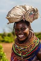 Smiling Nyangatom tribe woman with rows of beaded necklaces around her neck, Omo Valley, Ethiopia.