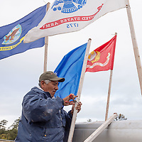 Ronald Daw prepares the flags for the veterans walk to the Navajo Nation Council Chambers in Window Rock on Wednesday.