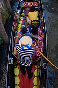 Aerial view of a gondolier and tourists in a narrow canal in Venice, Italy. The first mention ever of an Italian gondola was in Venice in 1094 and, of course, there have been gondoliers as long as there have been gondolas - so it's one of the oldest professions in the world. Until August 2010, there had never been a single woman gondolier in Venice as licences were always passed down to male family members. Current prices (2015) is 80 Euros for a 40-minute journey (earning them approx 130,000 Euros a year) along the waterways of this old city but rarely do gondoliers wear their straw hat.