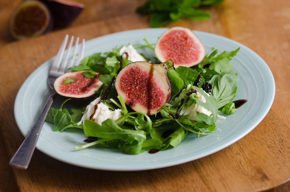 Fresh salad made of figs, mozzarella, rocket and basil