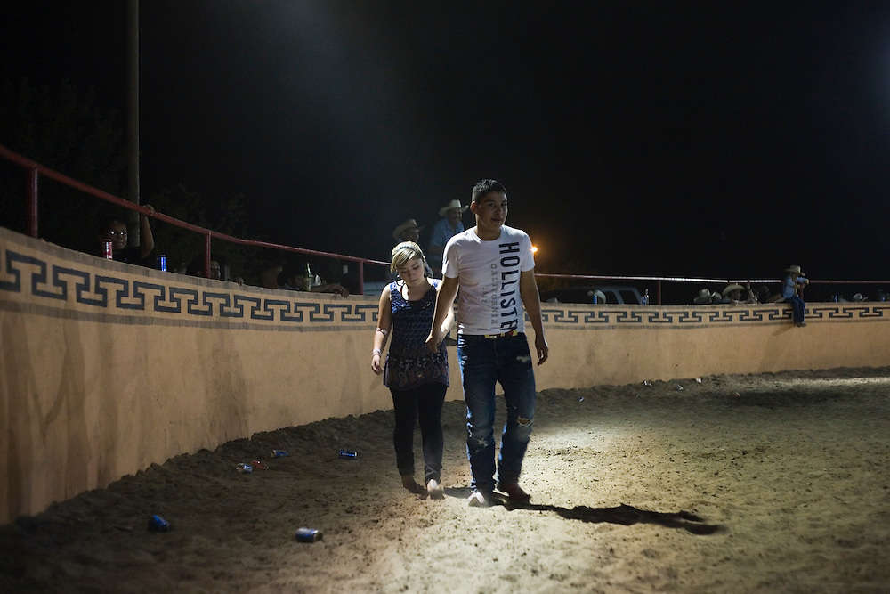 Julia Robinson photo.A young couple enters the liezo for a dance, or baile, at the end of a jaripeo at El Bajio in Von Ormy, Texas.  Live music is a popular addition to the charreada and draws crowds after the sun goes down.