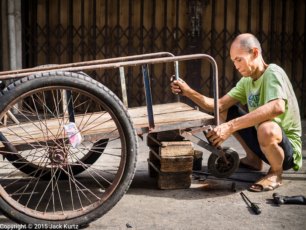 29 JUNE 2015 - BANGKOK, THAILAND: A man repairs a delivery cart in the Bang Chak Market in Bangkok. Bang Chak Market serves the community around Sois 91-97 on Sukhumvit Road in the Bangkok suburbs. About half of the market has been torn down, vendors in the remaining part of the market said they expect to be evicted by the end of the year. The old market, and many of the small working class shophouses and apartments near the market are being being torn down. People who live in the area said condominiums are being built on the land.     PHOTO BY JACK KURTZ
