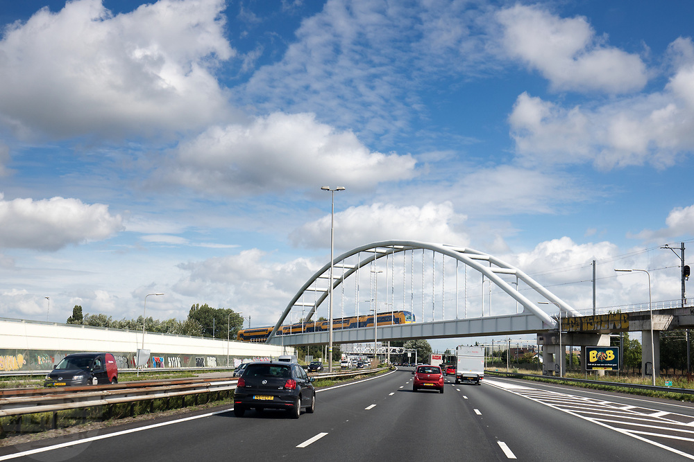 Bij Den Haag rijdt verkeer over de A12, een trein kruist over een spoorbrug.