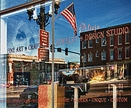 Window Reflection at Morrison Gallery in Geneva, IL shows the old State Bank Building and the old Hotel Geneva building.