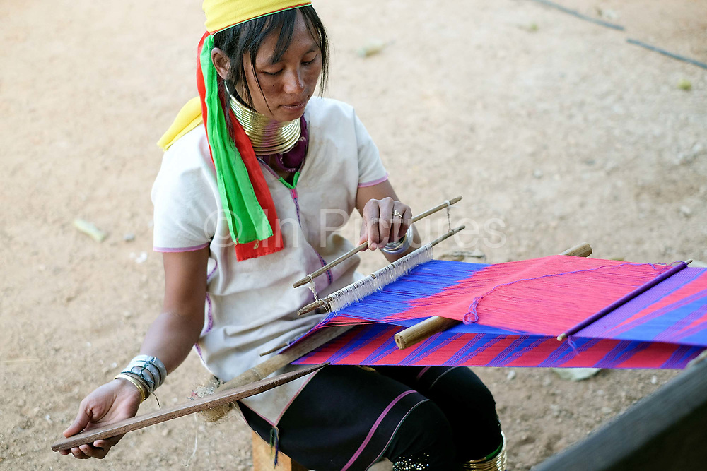 A Kayan Padaung ethnic minority woman weaving a skarf for tourists on 17 January 2016 in Kayah State, Myanmar. Myanmar is one of the most ethnically diverse countries in Southeast Asia with 135 different indigenous ethnic groups. There are over a dozen ethnic Karenni subgroups in the region including the Kayan who are perhaps the best known due to the traditional practice of the Kayan women extending their necks with brass rings