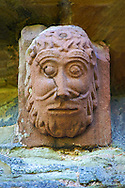 Norman Romanesque exterior corbel no 61 - sculpture of  a human head with curly hair and beard. The Norman Romanesque Church of St Mary and St David, Kilpeck Herefordshire, England. Built around 1140 .<br /> <br /> Visit our MEDIEVAL PHOTO COLLECTIONS for more   photos  to download or buy as prints https://funkystock.photoshelter.com/gallery-collection/Medieval-Middle-Ages-Historic-Places-Arcaeological-Sites-Pictures-Images-of/C0000B5ZA54_WD0s