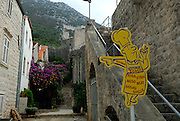Section of ancient wall and modern restaurant advertising sign, village of Ston, Croatia