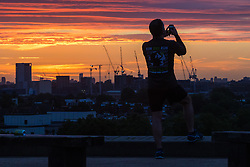 Primrose Hill, London, September 27th 2016. A man takes a picture of the city's skyline from Primrose Hill as dawn breaks over London. ©Paul Davey<br /> FOR LICENCING CONTACT: Paul Davey +44 (0) 7966 016 296 paul@pauldaveycreative.co.uk