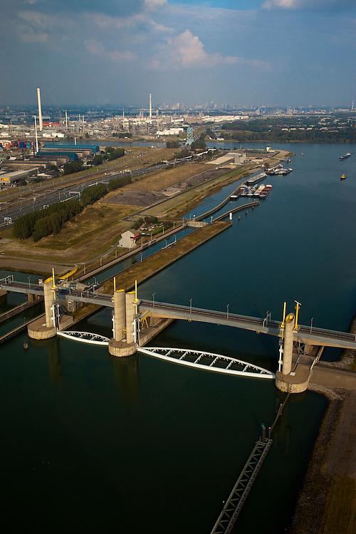 Nederland, Zuid-Holland, Botlek, 19-09-2009; Functioneringssluiting Hartelkering, de waterkering in het Hartelkanaal  wordt een maal per jaar, voordat het stormseizoen begint, getest. Tijdens  het sluiten van de kering ligt alle scheepvaartverkeer naar de Rotterdamse haven stil. .In de achtergrond Botlek en olieraffinaderij..De kering sluit normaal gesproken alleen bij dreigende stromvloed en bij een waterstand van 3 meter of meer boven NAP. De kering, onderdeel van de Deltawerken, vormt samen met de Maeslantkering  de Europoortkering en beschermt Rotterdam en achterland bij extreme waterstanden. .Netherlands, Rotterdam harbour. Aerial view of one of the two storm surge barriers. This barrier, the Hartelkering  in the Hartel canal, together with the greater nearby  Maeslant barrier (in the New Waterwy), are tested during the so-called functioning closure, taking place one a year before the storm season begins. The waterway and canal, leading to the Port of Rotterdam, are closed during the test..luchtfoto (toeslag), aerial photo (additional fee required).foto/photo Siebe Swart
