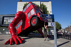 © licensed to London News Pictures. London, UK 23/07/2012. Czech artist David Cerny posing with his design the London Booster outside Business Design Centre. The double-decker bus has arms and does push ups outside Czech Team's Olympics headquarters in London during the Olympics. Photo credit: Tolga Akmen/LNP
