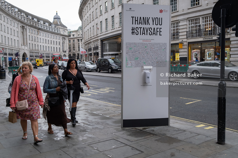 Three woman walk past a hand sanitiser post on Regent Street, during the Coronavirus pandemic, on 24th September, in London, England. New restrictions are being re-introduced by the government after a sudden climb in the Covid infection rate, a predicted 'second spike'.