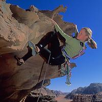 Climber Lisa Gnade ascends an overhang in Rakabat Canyon on Jebel (Mount) Um Ishram in Jordan's Wadi Rum, part of the Arabian Desert.