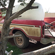 Eddie Hunter opens the valve on his 500-gallon truck mounted water tank so he can pump it into his 5,000-gallon storage tank at his home outside of Ash Fork.  Playing in the tree while Hunter transfers the water is his daughter, Sierra.