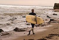 A man heads for the waves at Leadbetter Beach, Santa Barbara, California.