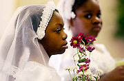 """May Crowning: St. Augustine Catholic Church  taylored their May Crowning ceremony to its African American students so they could """"get the peace and awarness of their own culture"""" said Father John Geaney. He used the Our Lady of Africa statue for the procession, where children bring flowers to honor Mary. Lakiah Morgan is in the foreground."""