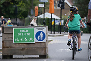 A young cyclist passes through the barriers that form an LTN (Low Traffic Neighbourhood), an experimental closure by Southwark Council preventing motorists from accessing the junction of Carlton Avenue and Dulwich Village. Restrictions also prevent traffic from passing through at morning and afternoon rush-hour times in the borough of Southwark, on 14th June 2021, in London, England.