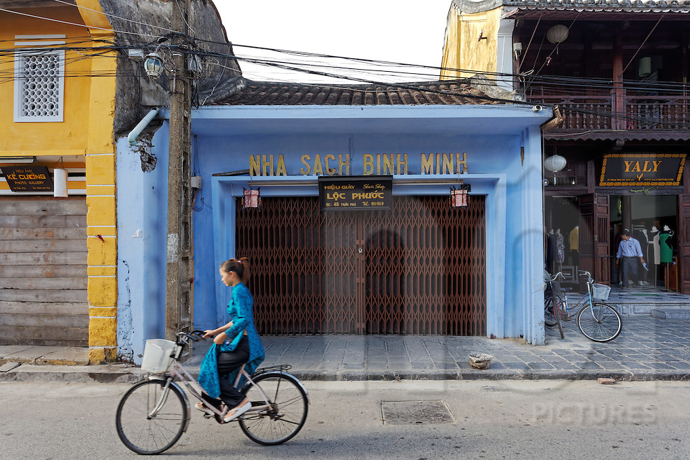 Young woman dressed in an Ao Dai rides her bicylce along the quiet streets of Hoi An early in the morning before shops have opened, Vietnam, Southeast Asia