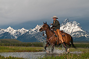 A wrangler and horse crossing a small creek with distant Grand Teton peaks in historic Jackson Hole, WY