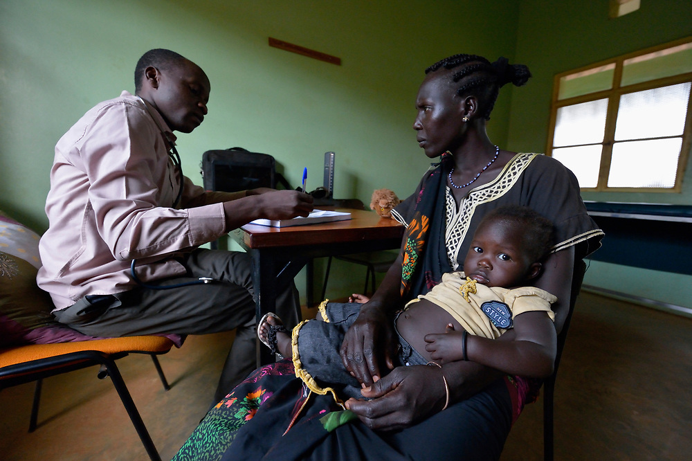 Dr. James Albino talks with a woman who brought her child to be examined in the St. Daniel Comboni Catholic Hospital in Wau, South Sudan.