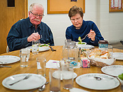 "26 FEBRUARY 2020 - FARMINGTON, MINNESOTA: GARY SMITH and DEE PARKER eat dinner at the community dinner at Faith Church, a United Methodist Church in Farmington, MN, about 30 minutes south of the Twin Cities. The dinner is sponsored by Loaves & Fishes, a Christian organization that provides food for community dinners and foodbanks. Farmington, with a population of 21,000, is a farming community that has become a Twin Cities suburb. The city lost its only grocery store, a Family Fresh Market, in December, 2019. Smith said he used to shop at the now closed several times a week but now he has drive much further to shop so doesn't shop as often. He also said he misses the community spirit the closed store, he and his friends used to meet there for coffee. The closing turned the town into a ""food desert."" In January, Faith Church started serving the weekly meals as a response to the store's closing. About 125 people per week attend the meal at the church, which is just a few blocks from the closed grocery store. The USDA defines food deserts as having at least 33% or 500 people of a census tract's population in an urban area living 1 mile from a large grocery store or supermarket. Grocery chains Hy-Vee and Aldi both own land in Farmington but they have not said when they plan to build or open stores in the town.     PHOTO BY JACK KURTZ"