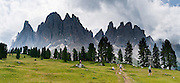 Hikers walk under the North faces of the Geisler/Odle Group, which drop nearly 1000 meters into Val di Funes (Villnöß valley) in the Dolomites, Italy, Europe. Puez-Geisler Nature Park (Italian: Parco naturale Puez Odle; German: Naturpark Puez-Geisler) is in Südtirol/South Tyrol/Alto Adige, in the Dolomiti, part of the Southern Limestone Alps, Italy. The Dolomites were declared a natural World Heritage Site (2009) by UNESCO.