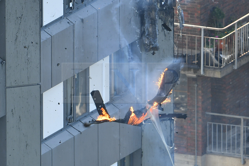 © Licensed to London News Pictures. 14/06/2017. London, UK. The fire continues to burn at the scene of a huge fire at a tower block in White City, London. The blaze engulfed the 27-storey building with 200 firefighters attending the scene. Photo credit: Ben Cawthra/LNP