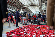 People attend a service of remembrance at Paddington's Platform 1, railways station during Armistice Day service in London, Wednesday, Nov. 11, 2020. Services held in many nations on Wednesday will commemorate the 102nd anniversary of the armistice ending World War I and honouring all those who died in the war. (VXP/ Vudi Xhymshiti)