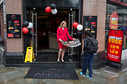 A member of staff with Angus Steakhouse shows their menu to passers-by on Coventry Street, on 13th August 2018, in London, England. Angus Steakhouse is the original chain of steak restaurants based in central Londons West End and has been serving both Londoners and visitors alike for 50 years.