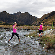 Runners Alex Musgrave. (right) and Naomi Richards  cross  Moke Creek on the Ben Lomond High Country Station during the Pure South Shotover Moonlight Mountain Marathon and trail runs. Moke Lake, Queenstown, New Zealand. 4th February 2012. Photo Tim Clayton