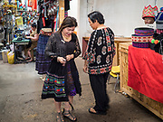 03 AUGUST 2019 - ST. PAUL, MINNESOTA: A woman tries on Hmong style skirt in the market at Hmongtown Marketplace. Thousands of Hmong people, originally from the mountains of central Laos, settled in the Twin Cities in the late 1970s and early 1980s. Most were refugees displaced by the American war in Southeast Asia. According to the 2010 U.S. Census, there are now 66,000 ethnic Hmong in the Minneapolis-St. Paul area, making it the largest urban Hmong population in the world. There are two large Hmong markers in St. Paul. The Hmongtown Marketplace has are more than 125 shops, 11 restaurants, and a farmers' market in the summer. Hmong Village is newer and has more than 250 shops and 17 restaurants.    PHOTO BY JACK KURTZ