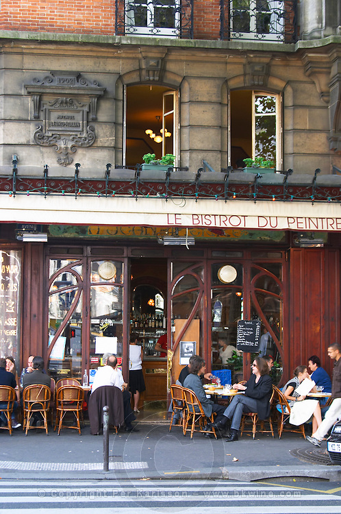 Le Bistrot du Peintre cafe bar terrasse terrase outside seating on the sidewalk. People sitting in chairs at tables eating and drinking outside at lunch time. The Bistrot du Peintre is an old fashioned Paris café cafe bar restaurant of art nouveau design with polished brass, mirrors and old signs