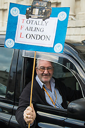 Whitehall, London, February 10th 2016. A taxi driver displays his placard as an estimated 8,000 cabbies hold a go-slow in protest against what they say is unfair competition from minicab and Uber drivers who do not have to undergo the rigorous training and checks required for the licenced taxi trade. ///FOR LICENCING CONTACT: paul@pauldaveycreative.co.uk TEL:+44 (0) 7966 016 296 or +44 (0) 20 8969 6875. ©2015 Paul R Davey. All rights reserved.