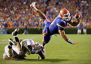 University of Miami vs. University of Florida in Gainesville, Fla. Third quarter...Florida quarterback Tim Tebow tosses the ball towards the goal line while he is brought down by Miami Colin McCarthy (44), under, and Darryl Sharpton (50) during the third quarter...AL DIAZ / MIAMI HERALD STAFF