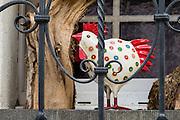 A chicken sculpture appears caged behind metal railing bars. Stein am Rhein, in Schaffhausen Canton, Switzerland, Europe.
