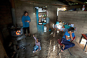 Pima farmer Jose Angel Galaviz Carrillo's wife Esthela makes tortillas by hand, cooking them on top of the wood stove, which also serves as a heat source during chilly Sierra Madre mountain winters a their home in Maycoba, Sonora, Mexico. (From the book What I Eat: Around the World in 80 Diets.) Her two youngest sons wait for breakfast, while her oldest son helps José with the milking. Practically self-sufficient, the family does buy some basic food and supplies, like powdered milk, at Disconsa, one of a network of government-subsidized stores catering to rural communities, in the town of Maycoba, six miles from their home. They grow their own corn and grind it, but Esthela keeps bags of masa flour on her pantry shelf for making tortillas. MODEL RELEASED.