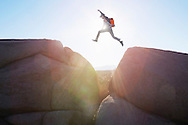 A man leaps over a large gap between two rocks with the bright sunlight glaring through.