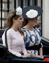 Princess Beatrice and Princess Eugenie ride in an open carriage during Trooping the Colour in London