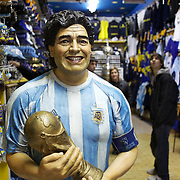 A statue of Diego Maradona in a shop selling Boca Juniors and Argentina football merchandise outside the famous Boca Juniors football stadium, La Bombonera, in La Boca region of Buenos Aires, Argentina, 25th June 2010. Photo Tim Clayton..
