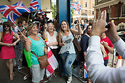 London, UK. Monday 22nd July 2013. Happy royalists wave their flags to camera. Media frenzy outside St Mary's Hospital in London on the day that Kate Middleton Duchess of Cambridge was taken into hospital after going into labour. Immediately the global media village began to buzz with activity and the Royalist public started to arrive in numbers.