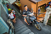 13 JANUARY 2013 - BANGKOK, THAILAND:  A man rides his motor scooter up the bridge ramp to cross Khlong Bang Luang in Bangkok. The Bang Luang neighborhood lines Khlong (Canal) Bang Luang in the Thonburi section of Bangkok on the west side of Chao Phraya River. It was established in the late 18th Century by King Taksin the Great after the Burmese sacked the Siamese capital of Ayutthaya. The neighborhood, like most of Thonburi, is relatively undeveloped and still criss crossed by the canals which once made Bangkok famous. It's now a popular day trip from central Bangkok and offers a glimpse into what the city used to be like.     PHOTO BY JACK KURTZ