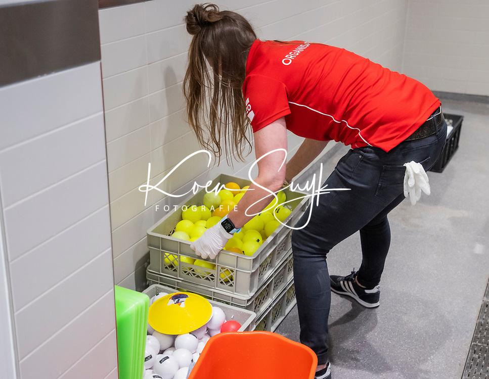 AMSTELVEEN -Tessa Krudde, medewerker van de KNHB , wast de ballen na afloop van de training.  de training van het heren hockey team. Het Nederlands elftal heeft toestemming gekregen van het ministerie van VWS, het RIVM en NOC NSF om de groepstrainingen te hervatten tijdens de coronacrisis.  COPYRIGHT KOEN SUYK