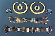 Ancient Egyptian jewellery.   In the centre of the middle item is a  carving of sacred scarab beetle.  British Museum, London.