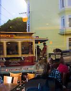 Cable car reflected in neighborhood cafe window, San Francisco, California
