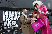 "The fine art character known as Pandemonia (part parody and living) is handed a free magazine featuring a model's eye on the cover on the first day of London Fashion Week, in the Strand, on 16th february 2018, in London, England. Pandemonia states  that she is ""a 7ft tall personality often seen at exclusive premiers, events and exhibitions. Post pop, conceptual artist, written about in iD, independent and Vogue publications."" Otherwise, few have any idea about who or what this cartoon character is, or even how this creature secures an invite to parties, society and art events. The writer Poonperm Paitayawat says "".. She is about branding, self-image and lifestyle. She is tapping into the collective unconsciousness. Pandemonia goes beyond pop art."""