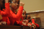 """From the front pew of Holy Name Cathedral, Christen Jones, 7 (in focus), listens to a homily with other Chicago Catholic School liturgical dancers during the 33rd Annual African American Heritage Month Eucharistic Celebration at Holy Name Cathedral. This year's mass celebrates the the Nguzo Saba principle of Kuumba, or """"creativity"""" at Holy Name Cathedral."""