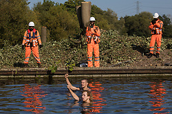 HS2 security guards monitor two anti-HS2 activists swimming in the Grand Union Canal to halt tree felling works alongside HOAC lake in connection with the HS2 high-speed rail link on 21 September 2020 in Harefield, United Kingdom. Anti-HS2 activists continue to try to prevent or delay works for the controversial £106bn HS2 high-speed rail link on environmental and cost grounds from a series of protection camps based along the route of the line between London and Birmingham.