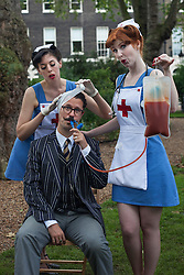 © licensed to London News Pictures. London, UK 08/07/2012. Two vintage nurse lookalikes posing with a man at the Chap Olympiad in Bedford Square Gardens in central London today.the Chap Olympiad describes itself as a celebration of eccentricity and athletic ineptitude with the emphasis on panache and style over sporting prowess. Photo credit: Tolga Akmen/LNP