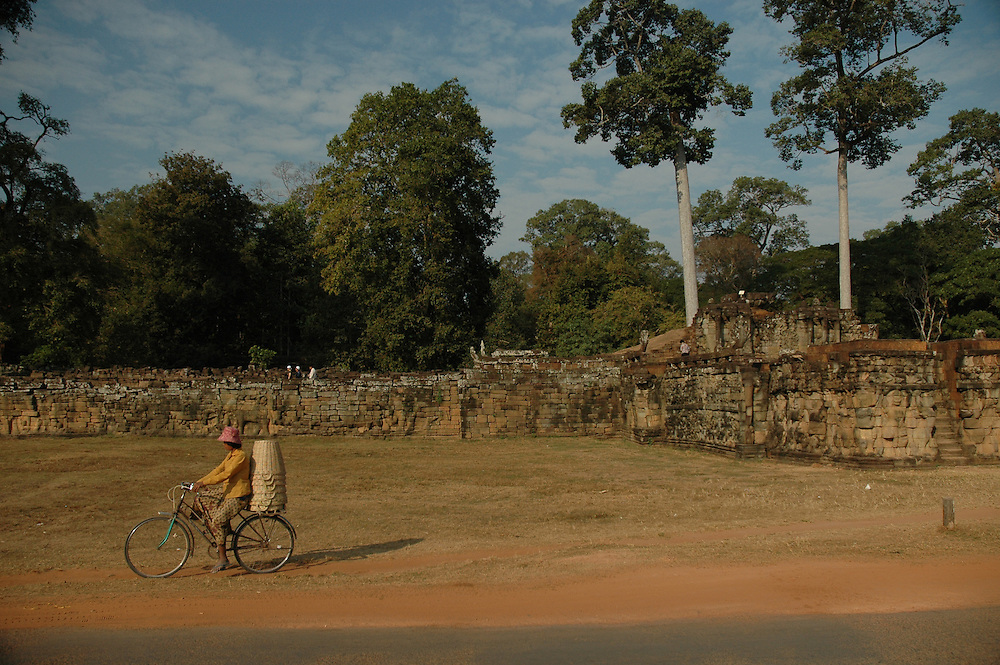 This woman riding a bicycle was shot in front of the Terrace of Elephants in Angkor Thom city, part of the Angkor complex in Siem Reap Cambodia that includes the world's largest single religious monument, the breathtaking Angkor Wat. <br /> <br /> The Terrace of Elephants, named  because of the elephant bas-reliefs on its wall and the elephant statues flanking the staircase, was used as a giant viewing platform for public ceremonies and extends for over 1000 feet (350 meters.) <br /> <br /> Angkor Thom, at the center of which lies the amazing Bayon temple is the last and most enduring city of the Khmer empire. It was built by King Jayavarman VII as a fortified city of almost 4 sq miles or 10 sq km on the right bank of the Siem Reap River, a tributary of Tonle Sap Lake.<br /> <br /> It has been featured in many book, films and video games of pop culture most notably in the Angelina Jolie film, Lara Croft: Tomb Raider.
