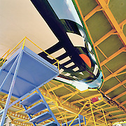 A Boeing 747 is surrounded by gantries during late night work by engineering staff who perform maintenance checks in the British Airways engineering hangar on the far side of London's Heathrow airport. As a landscape of confusing lines and linear design, we see the paintwork of the jet aircraft echoed in those of the platform struts and the steps that help the maintenance crews gain height and access to the high places required for the work to be carried out. At its tallest point, the 747's tail is 63 feet (19m).