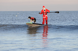 © Licensed to London News Pictures. 26/12/2013<br /> <br /> Saltburn, Cleveland, United Kingdom<br /> <br /> Hundreds of swimmers including a paddle boarding Santa and his dog brave the elements in fancy dress to take part in the annual Boxing Day dip on the beach in Saltburn, Cleveland to help raise money for a number of different charities.<br /> <br /> Photo credit : Ian Forsyth/LNP